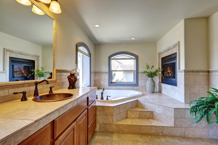 corner tub: Great bathroom interior in luxury house with fireplace, corner bathtub with stairs and tile trim. Northwest, USA Stock Photo
