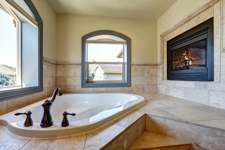 Great bathroom interior in luxury house with fireplace, corner bathtub with stairs and tile trim. Northwest, USA Stock Photo