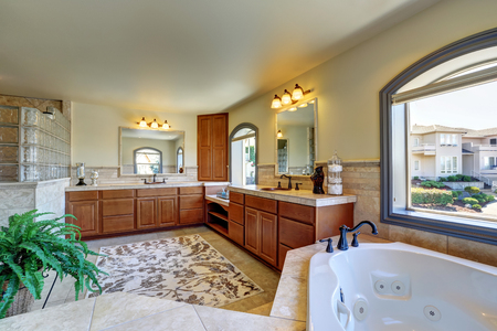 corner tub: Great bathroom interior in luxury house with corner bathtub and  master wooden cabinets with two sinks. Northwest, USA Stock Photo