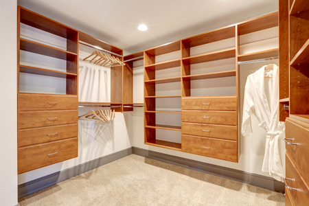 walk in closet: Large walk in closet with carpet floor, also including many shelves and drawers. Northwest, USA Stock Photo
