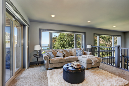 Grey interior of upstairs cozy family room with comfortable couch in luxury house. Soft carpet floor, leather ottoman and large window. Northwest, USA.