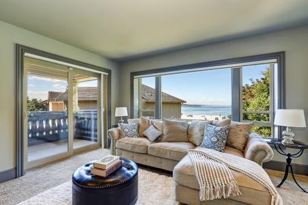 Interior gris de la habitación de la familia acogedora arriba con cómodo sofá en casa de lujo. para suelo suave, alfombras, cuero otomana y una ventana grande. Noroeste, EE.UU..