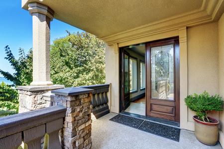 portada: exterior de la casa de lujo. Porche de entrada columna con barandillas y alfombra puerta abierta. Noroeste, EE.UU.