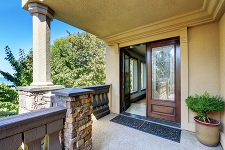 front house: Luxury house exterior. Entrance column porch with railings and rug Open front door. Northwest, USA