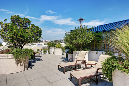 Apartment building roof top terrace exterior with lounge chairs and lots of greenery. Northwest, USA