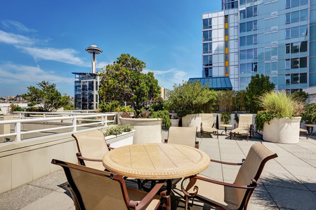 apartment building: Apartment building roof top terrace exterior with lounge chairs and patio table set. Northwest, USA