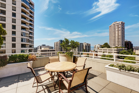 Apartment building roof top terrace exterior with patio table set and city view.  Northwest, USA