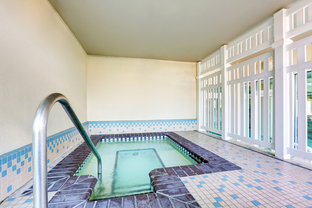 tile flooring: Interior of a swimming pool with Metal chrome plated ladder and tile flooring . Northwest, USA Stock Photo
