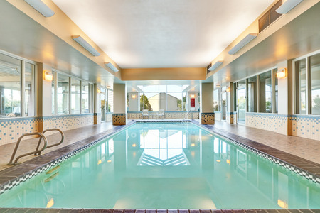 screened: Interior of a swimming pool with Metal chrome plated ladder and tile flooring. Northwest, USA