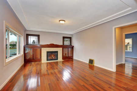 fireplace living room: Empty living room interior with polished hardwood floor. Fireplace with tile trim and cabinets. Northwest, USA Stock Photo
