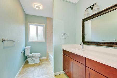 remodeled: Light blue remodeled bathroom with wooden vanity cabinet, toilet and bathtub, also tile floor. Northwest, USA