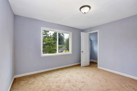 closet door: Empty room interior with lavender walls and beige carpet. Open door to a small walk-in closet. Northwest, USA