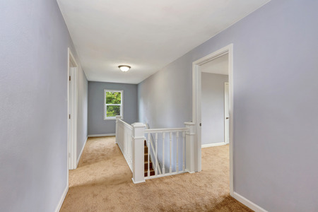 upstairs: Upstairs hallway interior in lavender color, white railings staircase and beige carpet floor. Northwest, USA Stock Photo