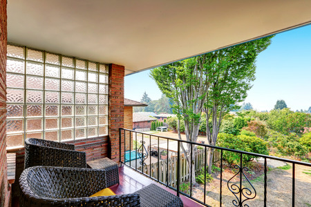 balcony: Balcony with wrought iron railing and black wicker chairs. Backyard view. Northwest, USA