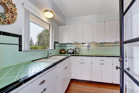cocina vieja: White empty simple old kitchen in American house. Green tile counter tops with black trim. Hardwood floor. Northwest, USA