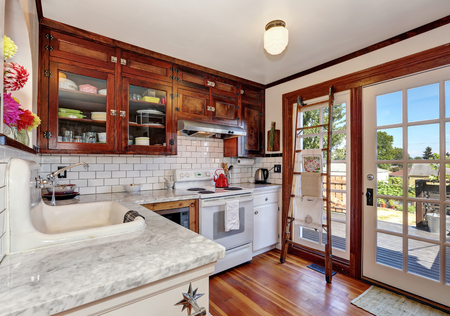 french doors: Vintage kitchen cabinets and white tile back splash trim. Kitchen interior. French doors lead to the back yard. Northwest, USA Stock Photo