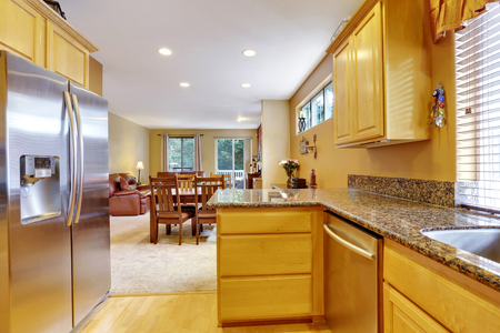 polished granite: Light tones kitchen interior with modern steel double doors fridge. Polished Granite counter tops. Dining room view. Northwest, USA