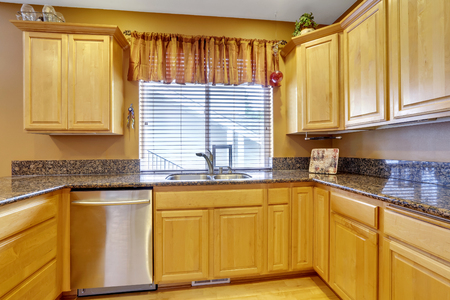 northwest: Light tones kitchen interior with modern golden tones cabinets with granite counter tops. Northwest, USA Stock Photo