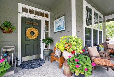 white trim: Cozy entrance porch with flower pots and seating arrangement. Northwest, USA Stock Photo