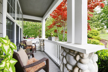 white trim: Cozy entrance porch with white columns decorated with stones and comfortable wicker chairs. Northwest, USA