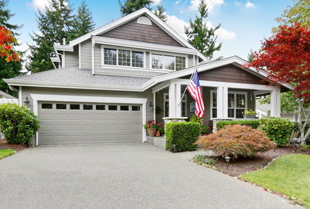 Nice curb appeal of grey house with garage and driveway. Column porch with American flag. Northwest, USA