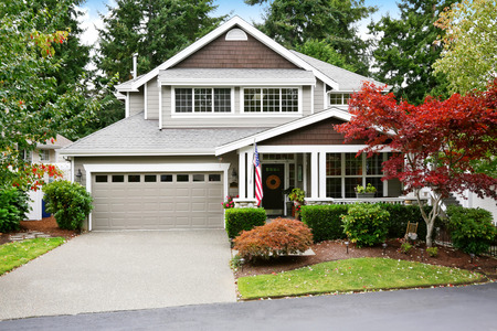 grey house: Nice curb appeal of grey house with garage and driveway. Column porch with American flag. Trimmed bushes and red maple tree. Northwest, USA Stock Photo