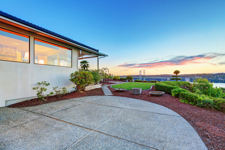 tacoma: Luxury house exterior at sunset. view of concrete floor patio area. Northwest, USA
