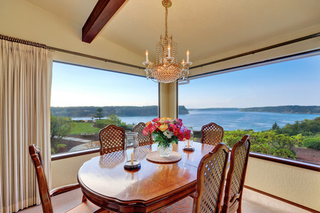 Dining room with carved wood table set and water view through the window. Tacoma, WA. Northwest, USA Stock Photo