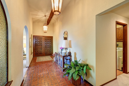 tile flooring: High ceiling hallway with pendant lights and brown tile flooring. Northwest, USA