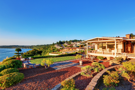 Luxury house exterior at sunset. Perfect landscape design. Scenic water view. Northwest, USA