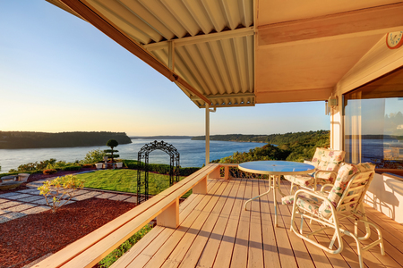 tacoma: Luxury house exterior at sunset. Wooden back deck with chairs and scenic water view. Northwest, USA