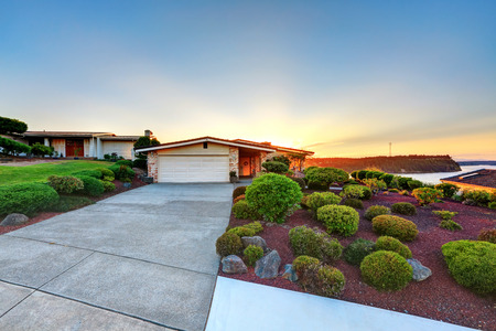 garage on house: Luxury House exterior. Garage with long concrete driveway. Perfectly trimmed yard. Northwest, USA Stock Photo