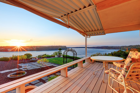 Luxury house exterior at sunset. Wooden back deck with chairs and scenic water view. Northwest, USA