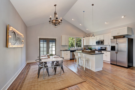 white kitchen: Interior of kitchen and dining room with high vaulted ceiling. white kitchen cabinetry and steel appliances. Antique chandelier above dining table. Northwest, USA