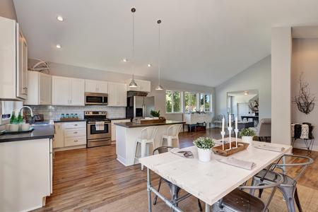cabinetry: Interior of kitchen and dining room with high vaulted ceiling. white kitchen cabinetry and steel appliances. Dining table with elegant setting. Northwest, USA