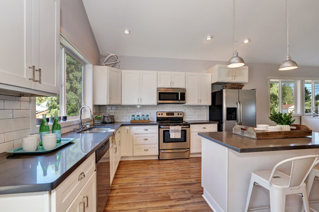cabinetry: Interior of kitchen with high vaulted ceiling, pendant lights, white kitchen cabinetry and steel appliances. Northwest, USA