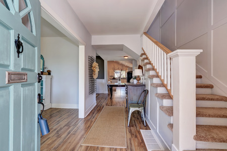 furnished: Nicely furnished hallway interior with vintage cabinet and white railings staircase. Northwest, USA Stock Photo