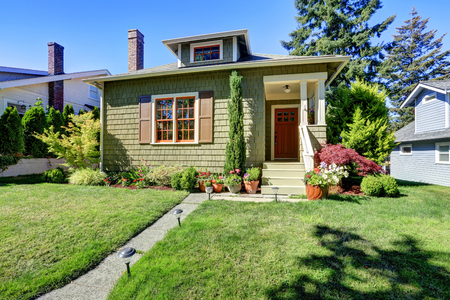 Small green American craftsman house exterior with entrance column porch. Northwest, USA