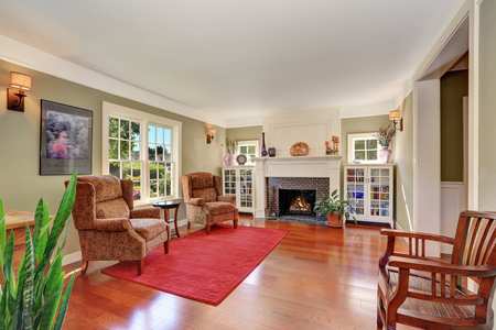 vintage furniture: Nice Living room with vintage furniture and red rug. Also brick fireplace, two bookcases and large french window. Northwest, USA