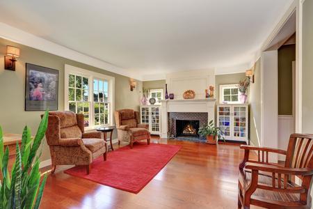 Schönes Wohnzimmer mit Vintage-Möbeln und roten Teppich. Auch gemauerten Kamin, zwei Regale und große französisch-Fenster. Northwest, USA Standard-Bild