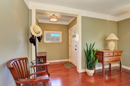 indoor inside: Hallway interior with olive walls and hardwood floor. Furnished with vintage wooden dresser and a chair. Northwest, USA