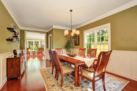 Brown and olive tones dining room interior. Large wooden table for six person. Northwest, USA