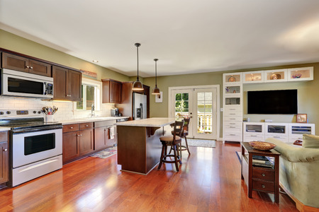 open plan: Open plan kitchen interior with Deep Brown storage combination and bar counter with two stools. French doors lead to back deck. Northwest, USA