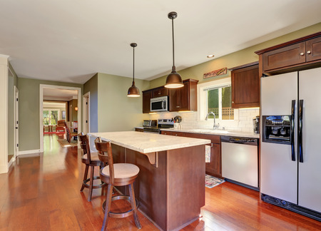 renovated: Deep Brown kitchen storage combination and bar counter with two stools and pendant lights. Northwest, USA