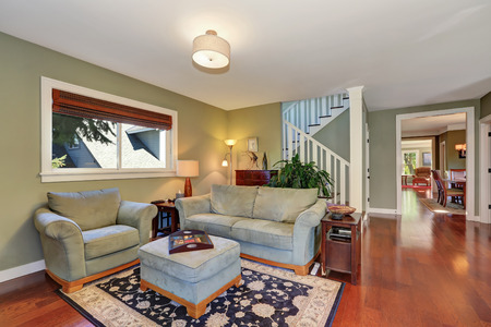 sitting area: Cozy sitting area with light olive sofa set and ottoman. Staircase view. Northwest, USA