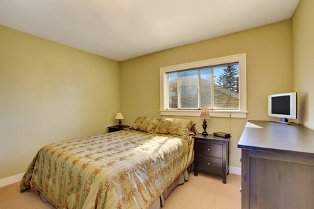 yellow walls: Simple bedroom interior with yellow walls. Bed with floral patterned bedding and nightstands. Northwest, USA