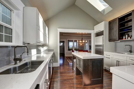 Modern style kitchen interior with brown and white cabinets, stainless steel appliances and vaulted ceiling with skylight. Northwest, USA