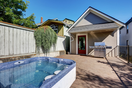 tacoma: Wooden walkout deck with hot tub and barbecue. Beige house exterior in Tacoma. Northwest, USA Stock Photo