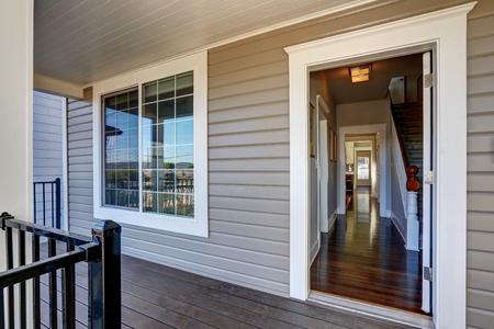 Lege overdekte veranda met een open voordeur en openslaande deuren. Northwest, USA
