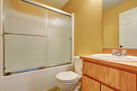 screened: Yellow walls bathroom with glass screened shower bathtub, toilet and wooden vanity cabinet. Northwest, USA Stock Photo